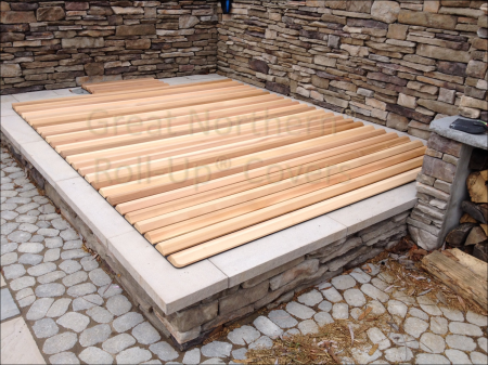 <p>Great Northern&reg; Western Red Cedar Roll-Up&reg; Cover on a stone spa</p>