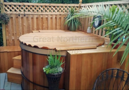 <p>Plants and privacy fence provide a private oasis for a Great Northern&reg; cedar Hot Tub and Roll-Up&reg; Cover</p>