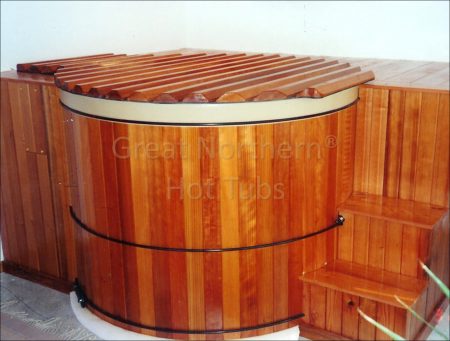 <p>Indoor round cedar Rubadub Tub&reg; Hot Tub in a custom surrounding wooden deck with steps, seating and a cabinet enclosing the spa equipment pack.</p>