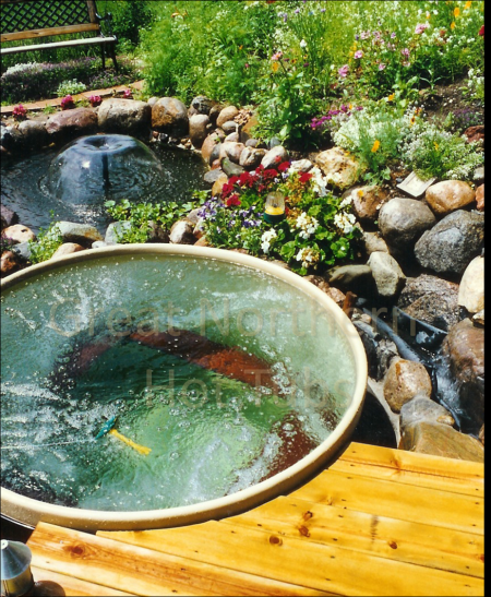 <p>Outdoor round wooden Great Northern Hot Tub off end of deck surrounded by a Rock Garden and pond</p>