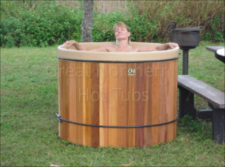 <p>woman inside a portable Great Northern cedar hot tub at a campground</p>