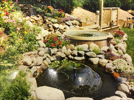 <p>Outdoor round wooden hot tub with small deck in a rock garden and pond.</p>
