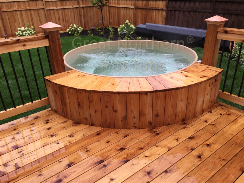 <p>Cedar Hot Tub with jets on next to deck in a backyard</p>