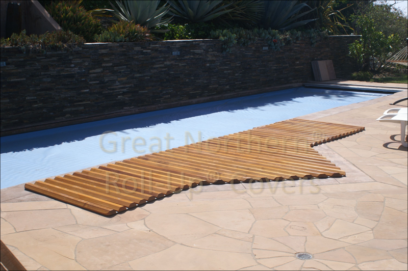 <p>Custom cedar roll-up cover on an in-ground poolside spa with a flagstone deck.</p>