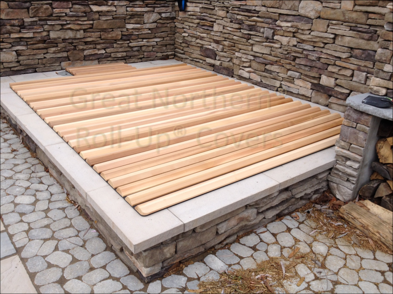 <p>Wooden roll-up cover on a rectangular in-ground stone spa.</p>