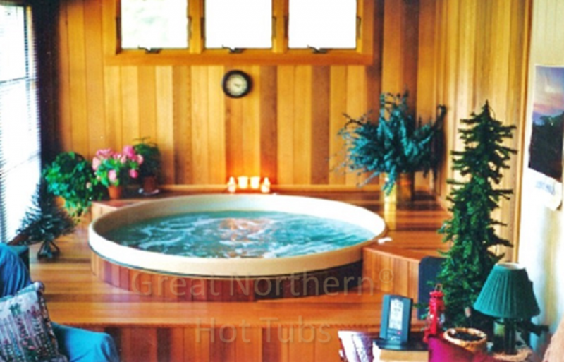 <p>Sunroom installation of a round cedar wood Hot Tub in a surrounding deck has steps and a recessed edge.</p>
