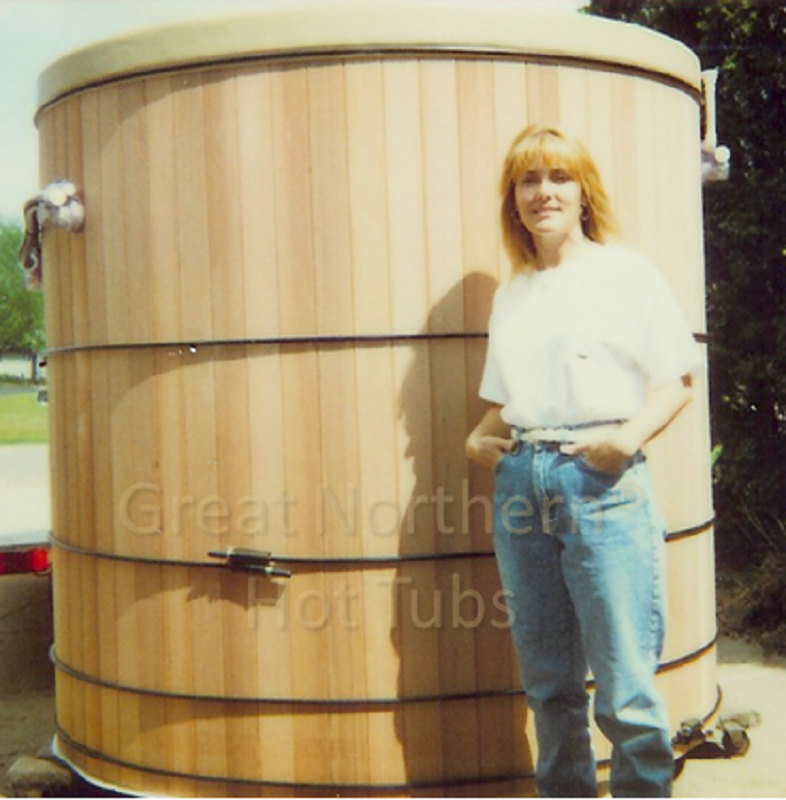 <p>Woman standing next to six-foot deep cedar wood hot tub. </p>