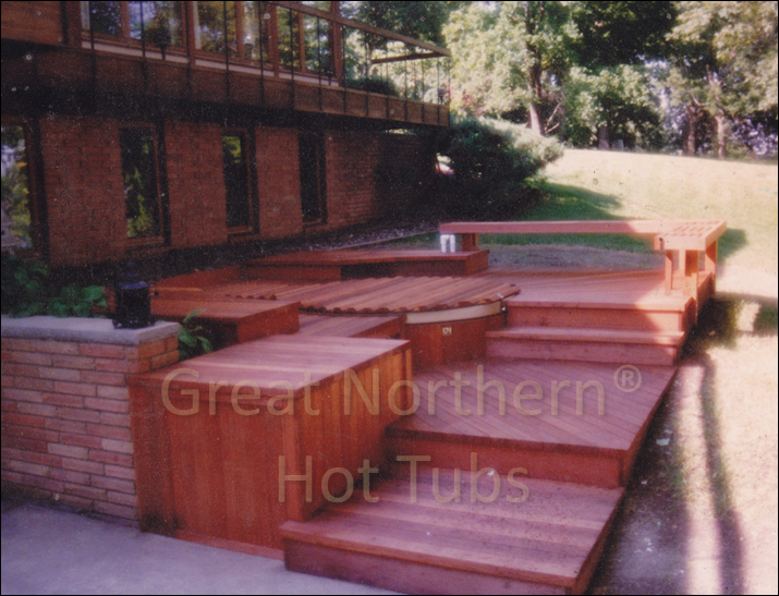 <p>Redwood hot tub built into a multi-level deck in a backyard patio-garden setting.</p>