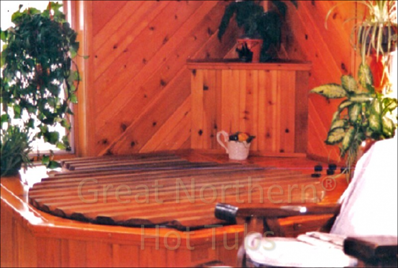 <p>Round hot tub surrounded by a small deck for easy seating located in the corner of a family room.</p>
