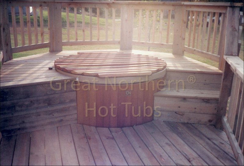 <p>Round cedar wood hot tub with unique wood roll-up cover in a 2 Level Deck with steps.</p>
