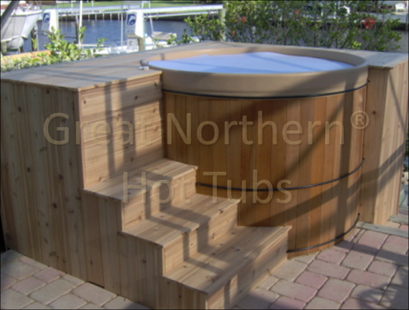 <p>Free-standing portable round cedar hot tub in a deck with steps.</p>