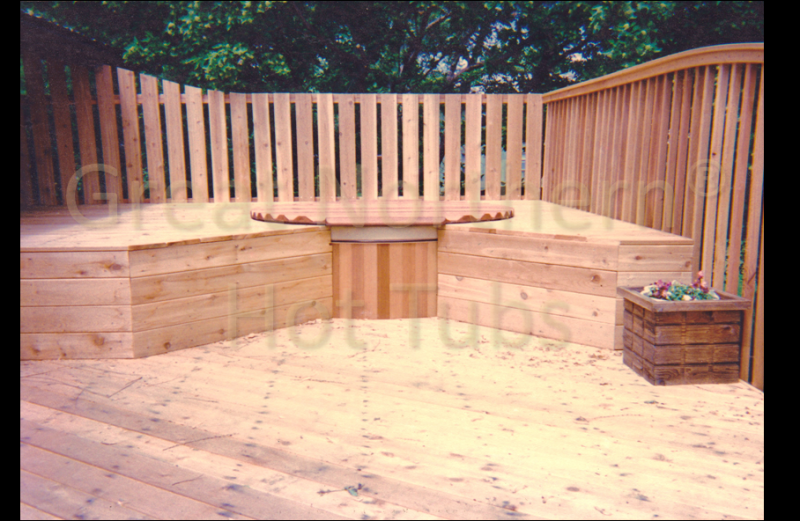 <p>Cedar hot tub on a large wood deck surrounded by a second level that provides flush seating around the tub.</p>