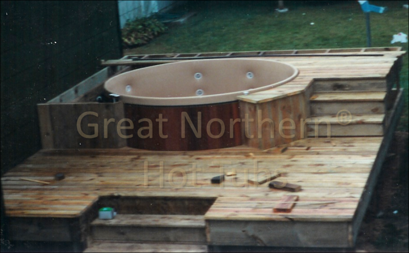 <p>Two-level deck being constructed around a cedar hot tub. Construction almost complete.</p>