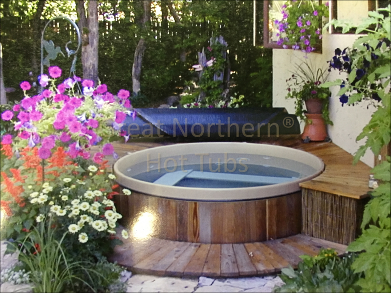 <p>Great Northern Rubadub Tub western red cedar hot tub with a rolled-up cover nearby with small surrounding deck in a garden setting.</p>