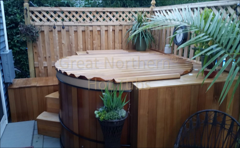 <p>A round cedar hot tub in a backyard corner with surrounding seating and a privacy fence.</p>